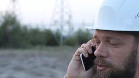 Bevindt de post technische directeur zich in een witte helm dichtbij de krachtcentrale en het spreken op de telefoon met de arbei stock video