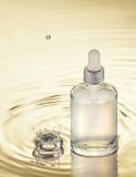 Bevochtigend serum op de gele waterachtergrond met plons en daling Stock Fotografie