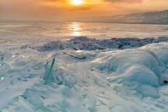 Bevroor watermeer met de achtergrond van de zonsonderganghemel, de wintertijd van Baikal Rusland stock fotografie
