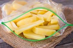 Bevroren aardappels in een zak op een houten lijst Bevroren Voedsel stock fotografie