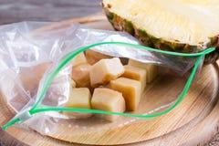 Bevroren ananaskubussen in een zak van hakbord royalty-vrije stock foto's