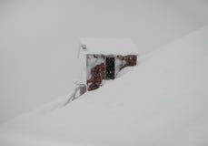 Bevroren cabine in profielmening over de sneeuwhelling van berg Stock Foto