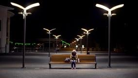 Bevroren dame die op laatste bus bij lege nachtpost wachten, die tijdschema controleren royalty-vrije stock foto's