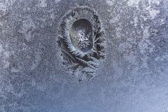 Bevroren de wintervenster met ontdooide vlek en grote bevroren waterdaling binnen het stock foto's
