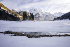 Bevroren die meer in sneeuw met sneeuwberg in de rug wordt behandeld stock fotografie