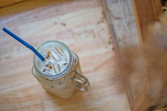 Bevroren koffie in kruik, de koppen van het mokglas op het houten tafelblad Stock Afbeeldingen