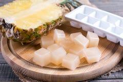 Bevroren kubussen van ananassap op de lijst stock fotografie