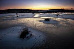 Bevroren meer bij zonsondergang in de winter Stock Afbeeldingen