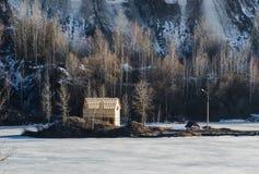 Bevroren meer met één huis in een bergland Royalty-vrije Stock Afbeeldingen