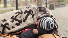 Bevroren mens die op de bank in park, die in deken liggen, armoede verpakken stock videobeelden