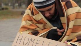 Bevroren mens omvat met deken die om aalmoes in de straat vragen, dakloosheid stock video