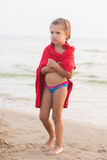 Bevroren oud die meisje van vijf jaar in een volwassen t-shirt wordt verpakt die zich op overzeese kust bevinden Royalty-vrije Stock Afbeeldingen