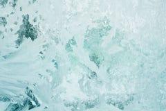 Bevroren patroon op het glazen venster in de winter en gekleurd in smaragd royalty-vrije stock fotografie