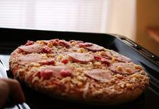 Bevroren pizza met salami, kaas, graan en peper Stock Fotografie
