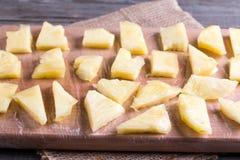 Bevroren plakken van bevroren ananas op een scherpe raad stock afbeeldingen