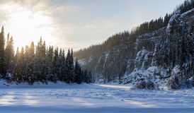 Bevroren rivier bij rotsachtige kust Stock Afbeelding