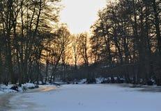 Bevroren rivier bij zonsondergang met bomen op de achtergrond Royalty-vrije Stock Afbeeldingen