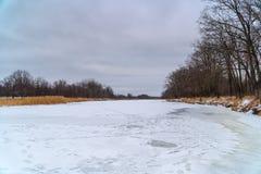 Bevroren rivier en bos in de afstand Het landschap van de winter royalty-vrije stock afbeelding