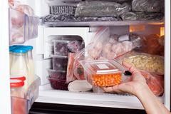Bevroren voedsel in de ijskast Groenten op de diepvriezerplanken Voorraden van maaltijd voor de winter stock foto