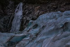 Bevroren vorming onder klip met waterval stock foto's