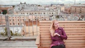 Bevroren vrouw in leerjasje Het zitten op de bank Voel koud op het dak in de wind stock video
