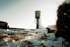Bevroren watertoren met grote ijskegels op landbouwbedrijf stock foto's