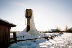 Bevroren watertoren met grote ijskegels op landbouwbedrijf royalty-vrije stock foto