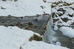 Bevroren waterval van bergstroom in het midden van sneeuw en ro Royalty-vrije Stock Afbeelding
