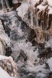 Bevroren weinig waterstroom in de winterlandschap stock afbeelding