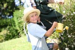 Bewässerungsanlagen des kleinen Jungen mit seinem Vater Stockbilder