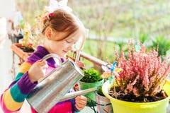 Bewässerungsanlagen des kleinen Mädchens auf dem Balkon Stockbild