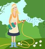Bewässerungsblumen der jungen Frau in einem Garten Stockfotografie