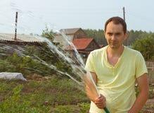 Bewässerungsgarten des Mannes am Sommernachmittag Lizenzfreie Stockfotos