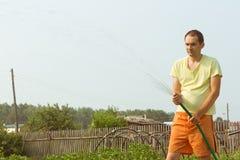 Bewässerungsgarten des Mannes am Sommernachmittag Stockfoto