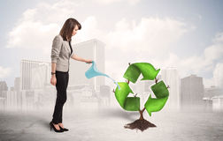 Bewässerungsgrün der Geschäftsfrau bereiten Zeichenbaum auf Stadt backgrou auf Lizenzfreie Stockbilder