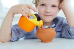 Bewässerungstopf des kleinen Jungen mit Münzen Frühe Wirtschaftspädagogik lizenzfreie stockbilder