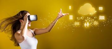 Bewölken Sie die Datenverarbeitung mit der Frau, die einen Kopfhörer der virtuellen Realität verwendet Stockfotografie
