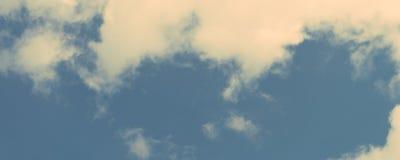 Bewölken Sie sich auf Hintergrund des blauen Himmels - Retro- Weinleseeffekt-Artbilder Panoramische Fahne Stockfoto