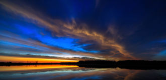 Bewölken Sie sich in der Himmel beleuchteten Morgendämmerung, reflektiert im Wasser Stockfotografie