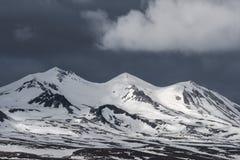 Bewölkte Himmel über Schnee-mit einer Kappe bedeckten Bergen in Island Stockfotografie