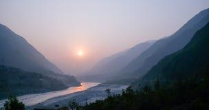 Bewölkte Landschaftsansicht des Sonnenuntergangs über Fluss Indus und Schichten Karakoram-Gebirgszug, Pakistan lizenzfreie stockfotos