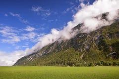 Bewölkte Spitzen und Wiese in den Alpen Stockfotos