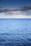 Bewölkter blauer Himmel, der für Horizontblaues Oberflächenmeer verlässt stockfotografie