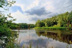 Bewölkter Himmel über dem ruhigen Fluss Stockfoto