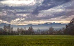Bewölkter Himmel über den Hügeln und den Bauernhofweiden stockfotos