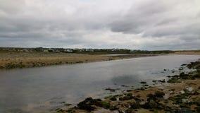 Bewölkter Himmel über einem Strand in Irland Stockbild