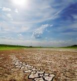 Bewölkter Himmel über gebrochener Erde Lizenzfreies Stockfoto