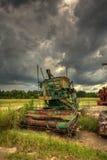 Bewölkter Himmel über verlassenen landwirtschaftlichen Maschinen Lizenzfreie Stockbilder