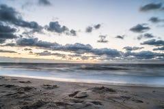 Bewölkter Himmel auf Ozean und Sand Lizenzfreie Stockbilder