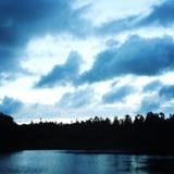 Bewölkter Himmel auf Sonnenuntergang See und Forest Silhouette lizenzfreie stockfotos